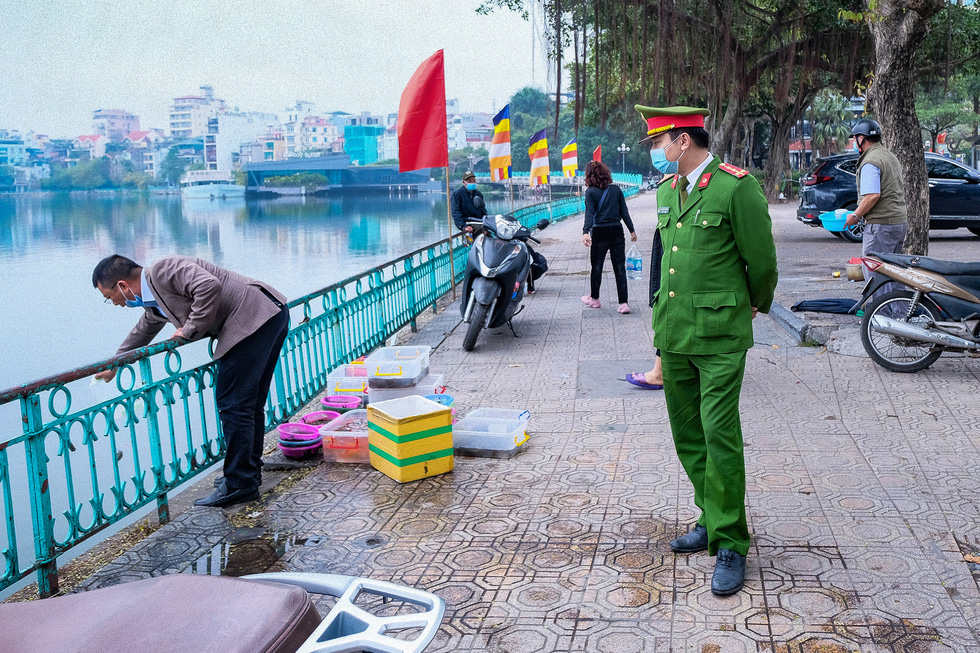 Vendors selling animals for mercy release in front of Tran Quoc Pagoda in Tay Ho District are forced to move by police officials, February 16, 2021. Photo: Nam Tran / Tuoi Tre