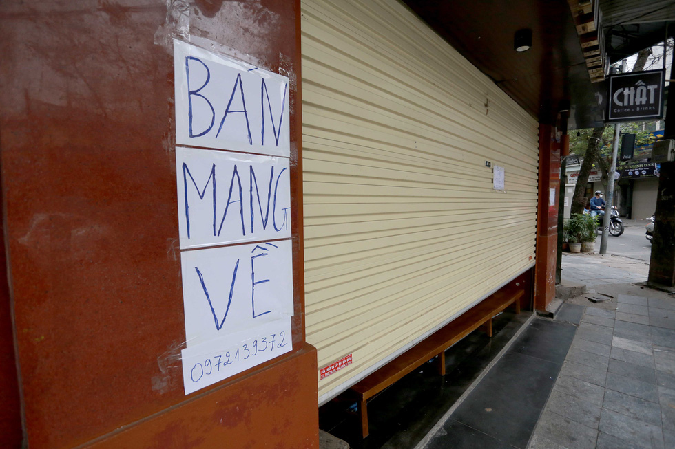 """Ban mang ve"" (Takeaway available) sign on a coffee shop on Hanoi's Hang Bong Street, February 16, 2021. Photo: Nam Tran / Tuoi Tre"