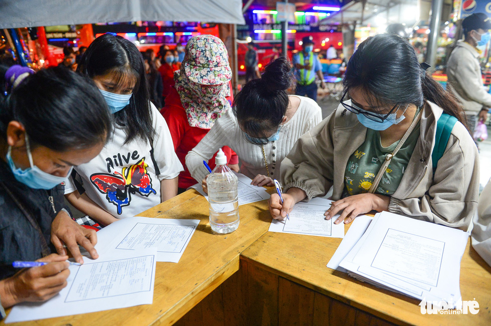 Passengers at Eastern Bus Station of Ho Chi Minh City fills in information form before undergoing COVID-19 testing, February 18, 2021. Photo: Quang Dinh / Tuoi Tre