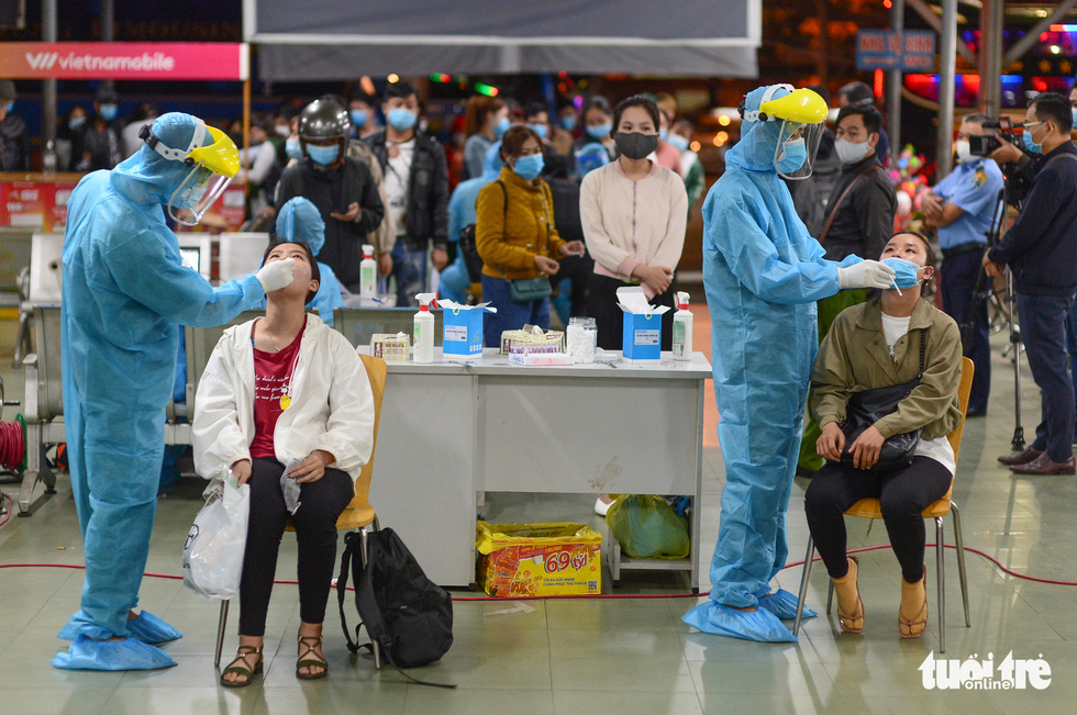 Health workers obtains sample for COVID-19 testing from passengers at Eastern Bus Station of Ho Chi Minh City, February 18, 2021. Photo: Quang Dinh / Tuoi Tre