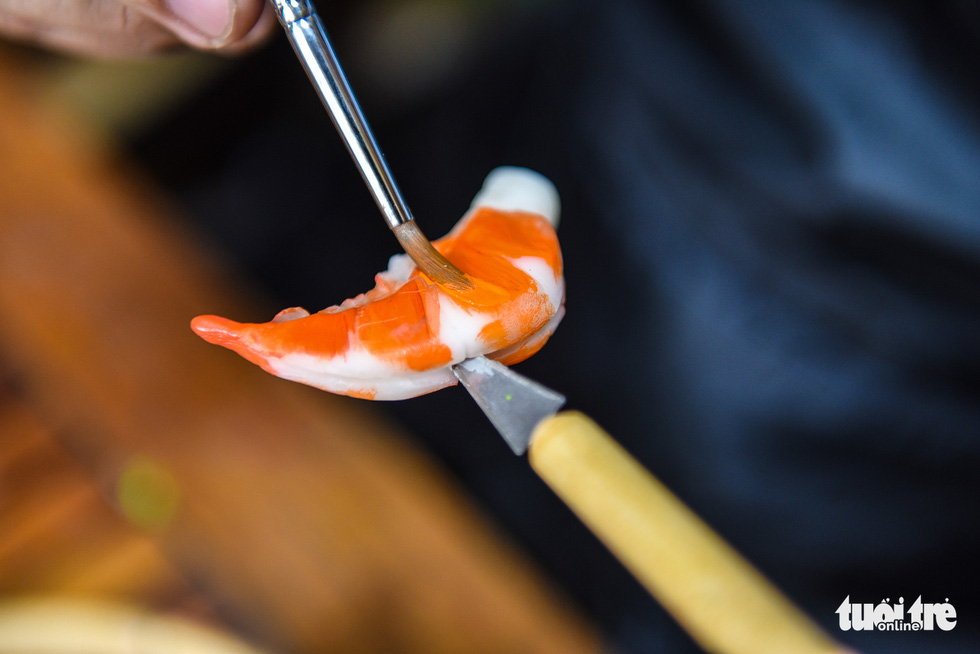 Dat adds color to a shrimp made of clay. Photo: Ngoc Phuong / Tuoi Tre