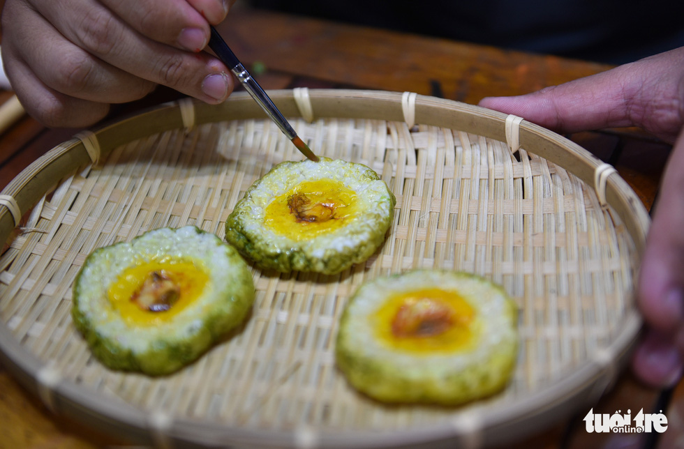 Dat paints on a slice of 'banh tet,' one of the most popular dishes during Tet Holiday in southern Vietnam. Photo: Ngoc Phuong / Tuoi Tre