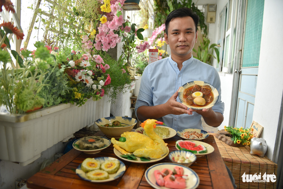 Dat poses besides the traditional dishes that he spent more than one month making them. Photo: Ngoc Phuong / Tuoi Tre