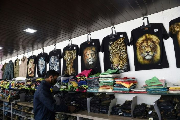 In this picture taken on January 5, 2021 a shopkeeper arranges garments bearing pictures of lions and leopards at a souvenir shop at the Gir National Park and Sanctuary at Sasan Gir, some 330 kilometers from Ahmedabad. Photo: AFP