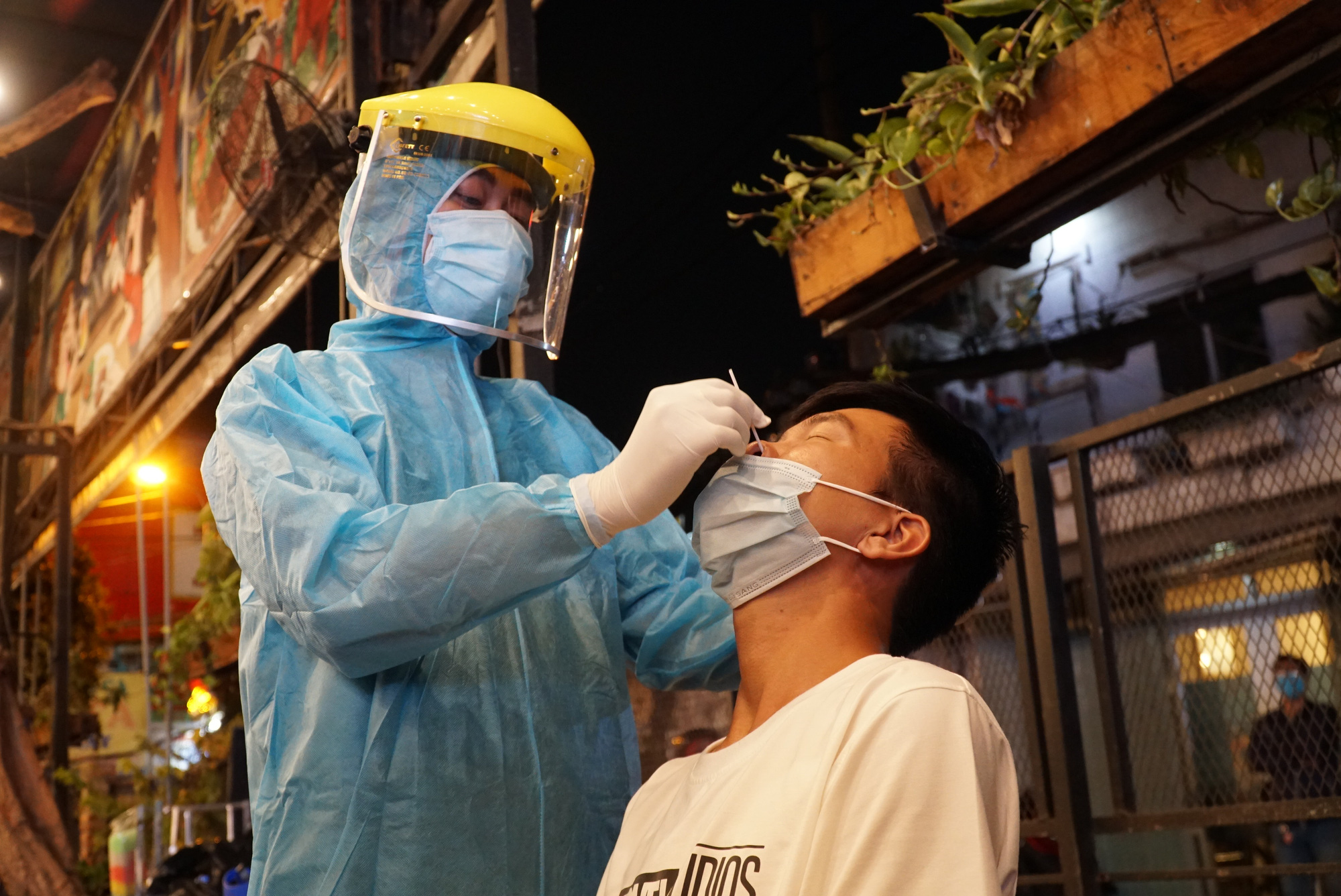 A medical worker samples a man at a restaurant in Ward 11, Binh Thanh District, Ho Chi Minh City, February 22, 2021. Photo: Dan Thuan / Tuoi Tre