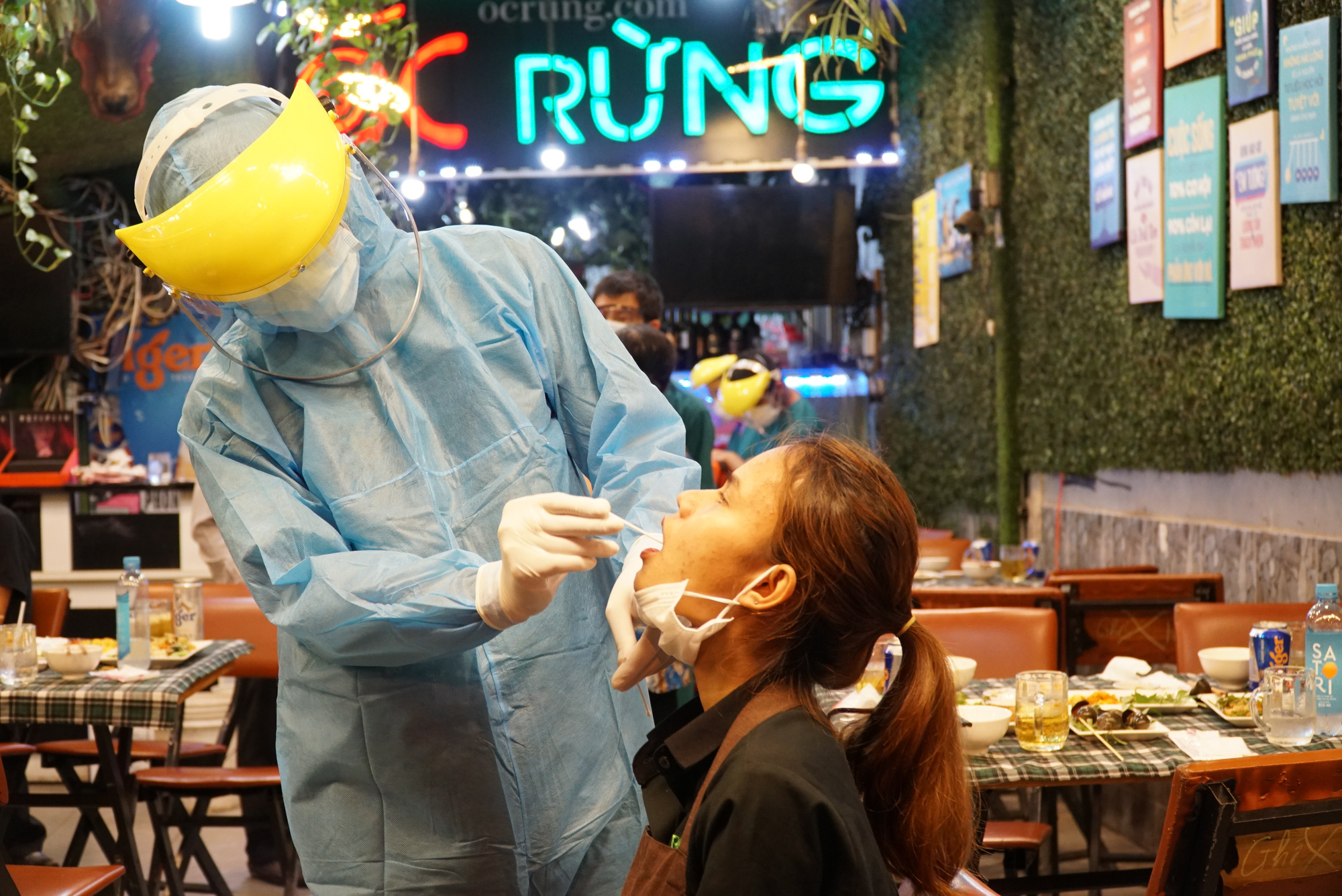 A medical worker samples a woman at a restaurant in Ward 11, Binh Thanh District, Ho Chi Minh City, February 22, 2021. Photo: Dan Thuan / Tuoi Tre