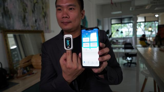 Nervotec founder Jonathan Lau shows the comparison in vital signs readings between his company's app and a pulse oxygen monitor, in Singapore, February 19, 2021. Photo: Reuters