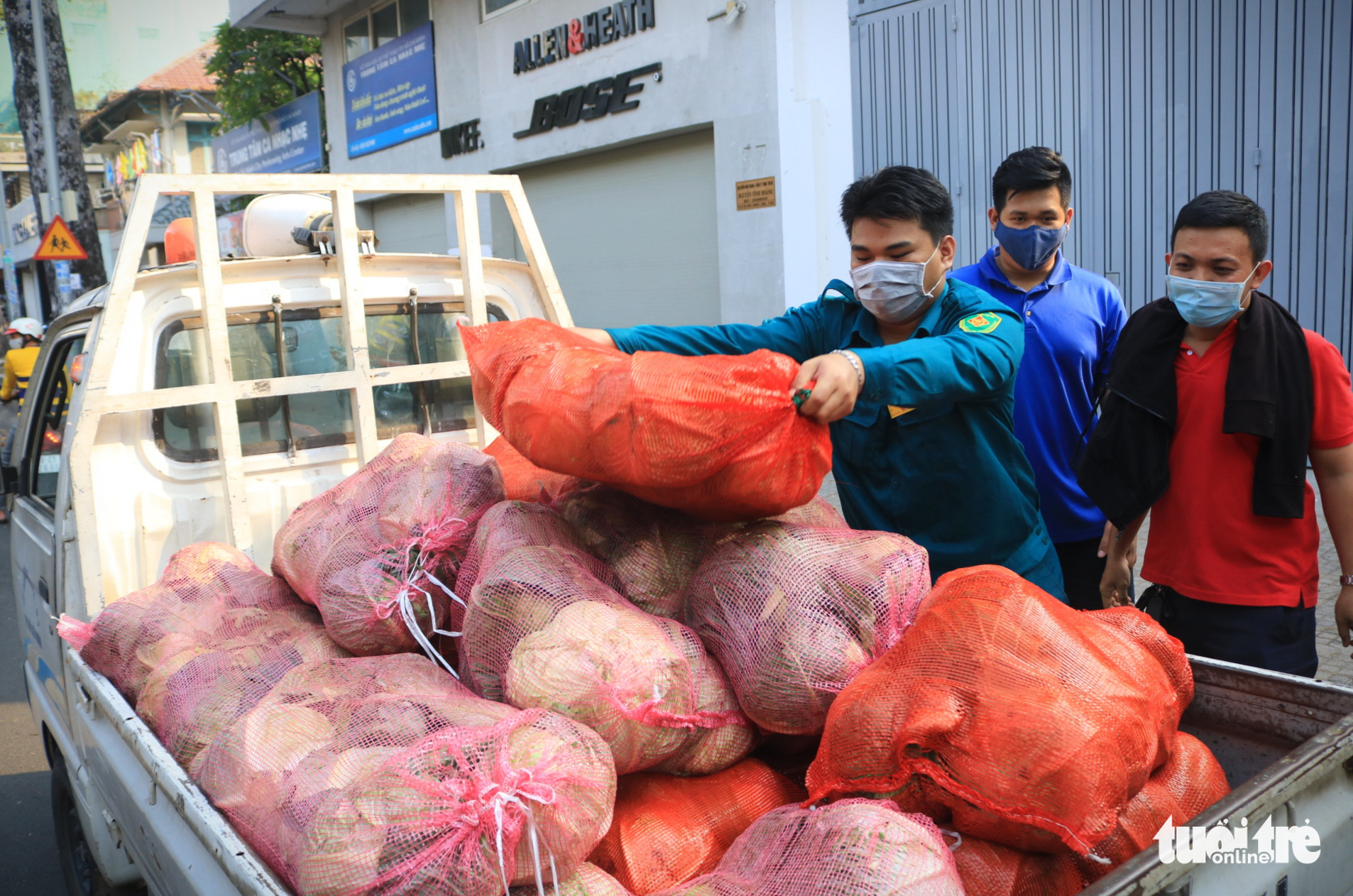 Large bags of cabbage from northern Hai Duong Province are loaded onto a mini truck in District 3, Ho Chi Minh City, February 23, 2021. Photo: Nhat Thinh / Tuoi Tre