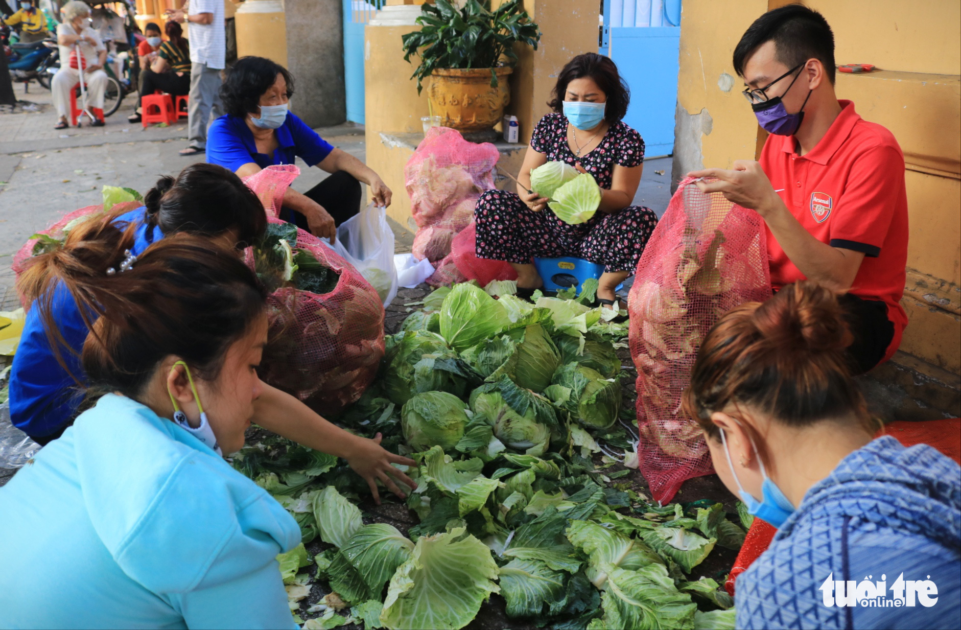 Enthusiastic people help at a makeshift stall of cabbage rescued from northern Hai Duong Province in District 3, Ho Chi Minh City, February 23, 2021. Photo: Nhat Thinh / Tuoi Tre