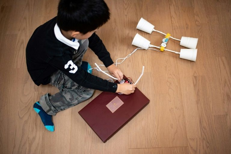 This picture taken on December 9, 2020 shows Akito Takahashi playing with a handmade robot kit at his apartment in Tokyo. Photo: AFP