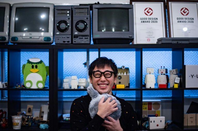 In this picture taken on December 8, 2020 shows Shunsuke Aoki, CEO of Yukai Engineering hugging robotic cushion Qoobo n a studio in Tokyo. Photo: AFP