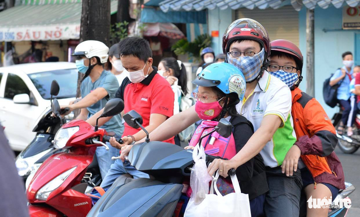 Parents take their children to school in District 4, Ho Chi Minh City, March 1, 2021. Photo: Tu Trung / Tuoi Tre