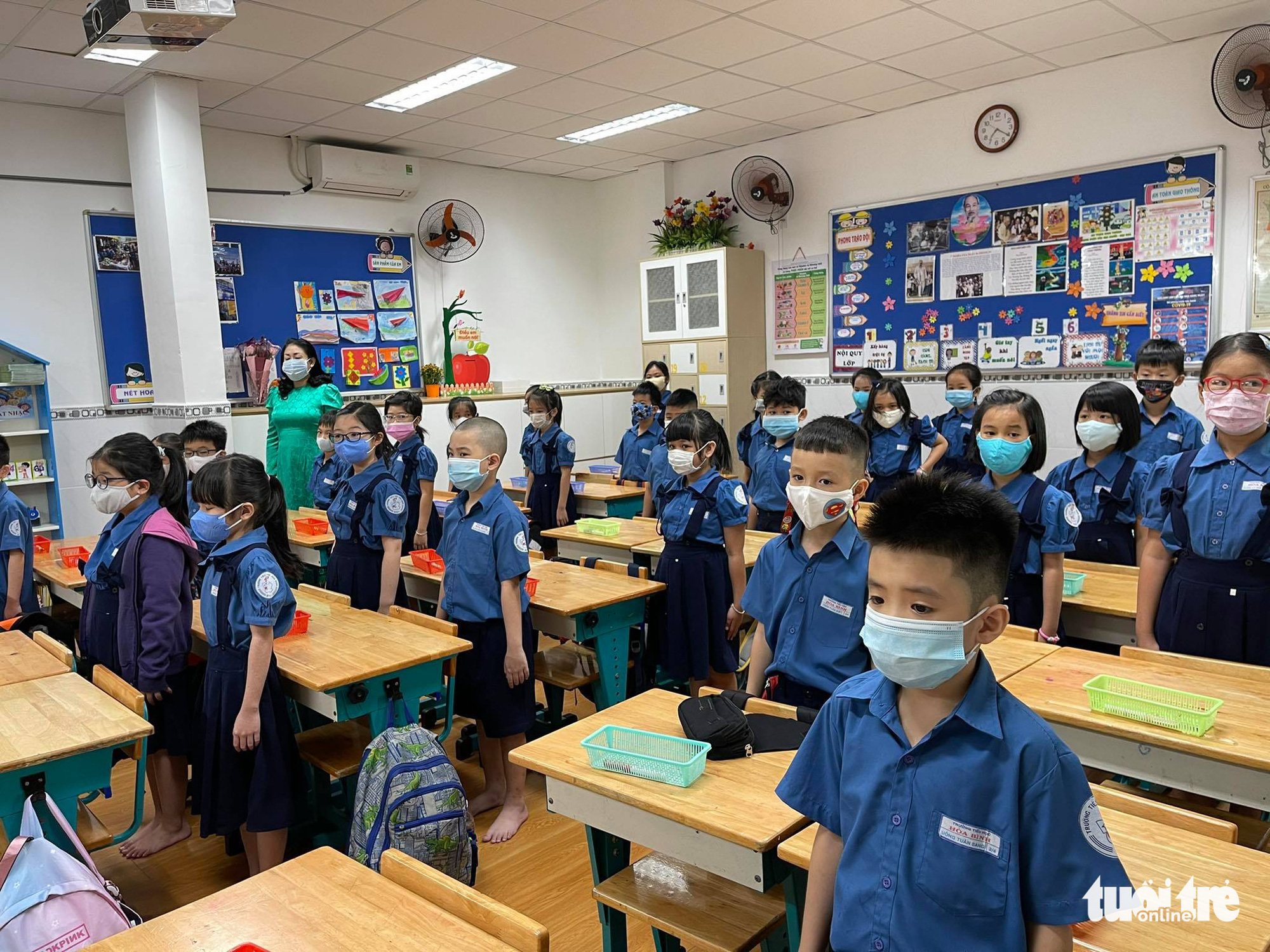 Students attend the flag salute ceremony inside a classroom at Hoa Binh Elementary School in District 1, Ho Chi Minh City, March 1, 2021. Photo: Thao Thuong / Tuoi Tre