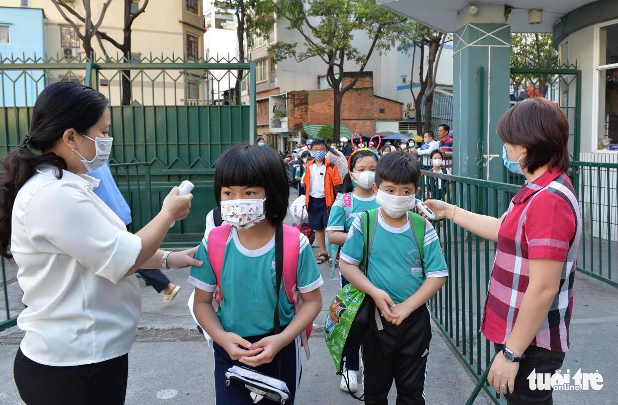 Students have their body temperature measured at Nguyen Van Troi Primary School in District 4, Ho Chi Minh City, March 1, 2021. Photo: Tu Trung / Tuoi Tre