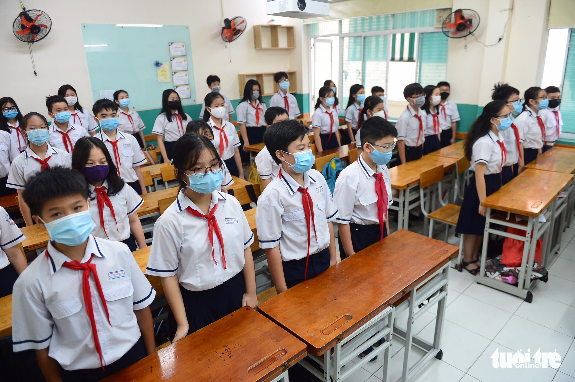 Students attend the flag salute ceremony inside a classroom at Nguyen Du Middle School in District 1, Ho Chi Minh City, March 1, 2021. Photo: Quang Dinh / Tuoi Tre