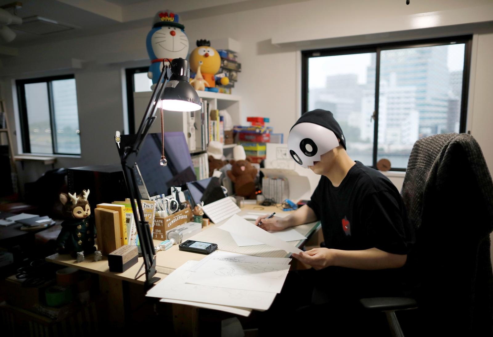 Japanese manga artist Kamentotsu, who goes by his pen name and wears a mask in media appearances, draws his four-panel strip comic 'Koguma's Cake Shop' at his workspace in Tokyo, Japan October 8, 2020.  Photo: Reuters