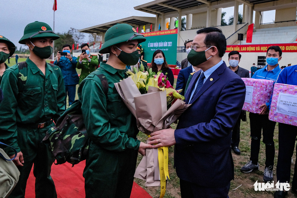Vuong Dinh Hue, secretary of the Hanoi Party Committee, hands flowers to a military enlistee in the rookie handover ceremony in Hanoi's Dong Anh Province, February 27, 2021. Photo: Nam Tran / Tuoi Tre
