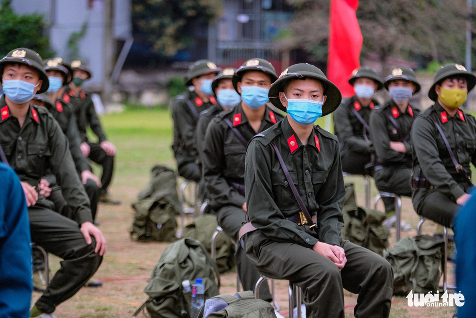 Enlistees from Hanoi's Dong Anh Province sit far apart the in the rookie handover ceremony, February 27, 2021. Photo: Nam Tran / Tuoi Tre