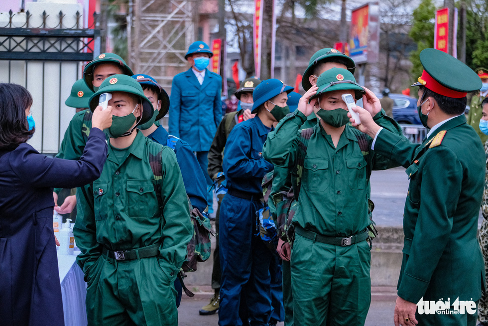 Enlistees from Hanoi's Dong Anh Province undergo body temperature check in the rookie handover ceremony, February 27, 2021. Photo: Nam Tran / Tuoi Tre