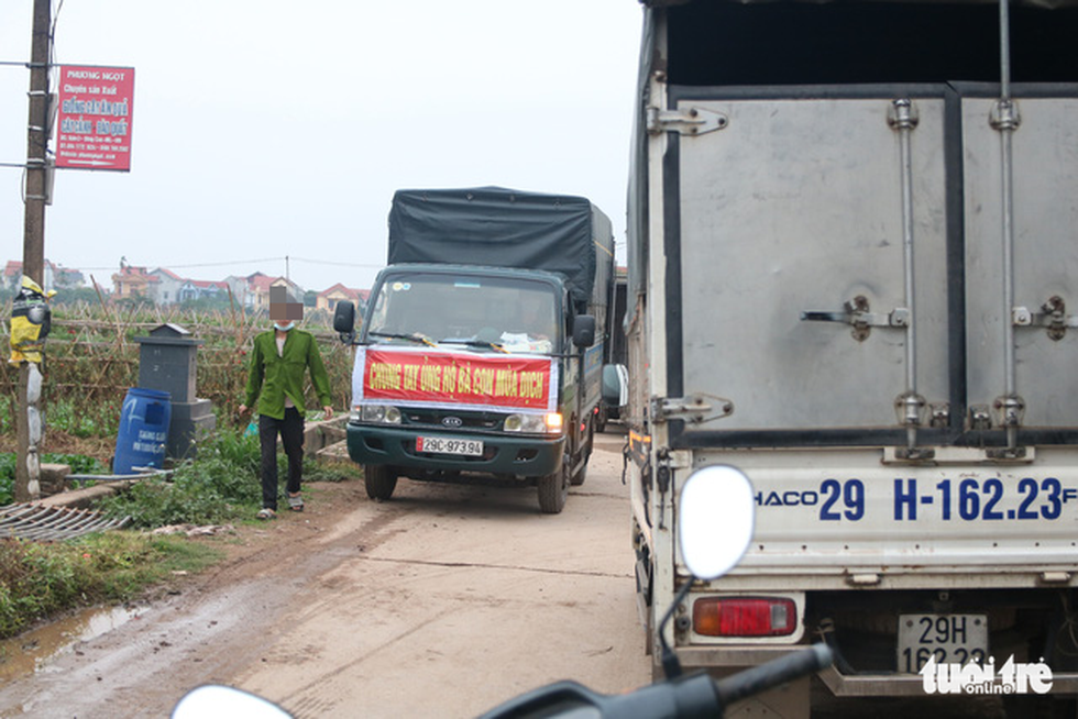 "Trucks with banners saying ""joining hands to help farmers sell vegetable amid the pandemic"" run to and from the Dong Cao Village. Photo: Ha Quan/Tuoi Tre"