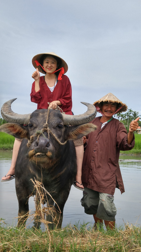A tourist poses with a buffalo and his owner. Photo: B.D / Tuoi Tre