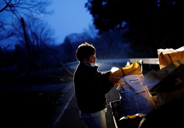 Sakae Kato prepares to feed wild boars in front of his home, in a restricted zone in Namie, Fukushima Prefecture, Japan, February 20, 2021. Photo: Reuters