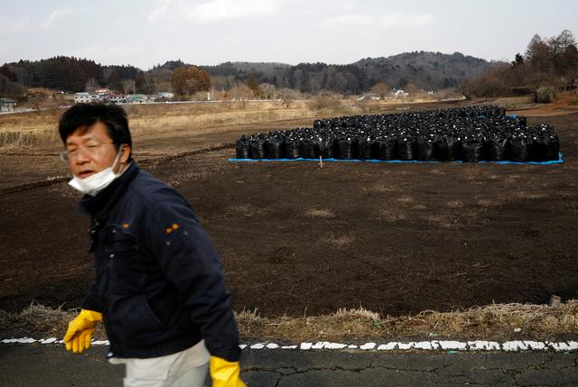 Sakae Kato walks past black bags containing contaminated soil from the fallout of the Fukushima nuclear plant, in a restricted zone in Namie, Fukushima Prefecture, Japan, February 21, 2021. Photo: Reuters