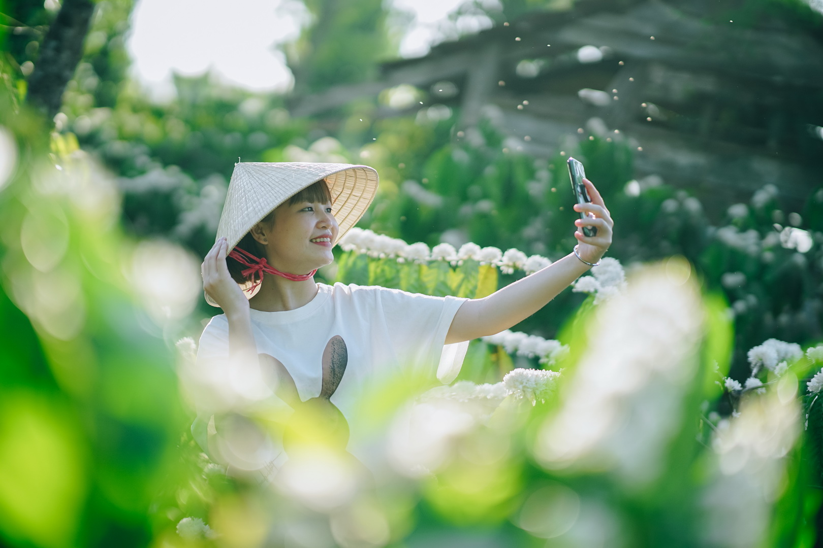 A woman takes selfies against the white blossoming coffee flowers in a Robusta garden in the Central Highland Province of Dak Lak. Photo: Van Nguyen