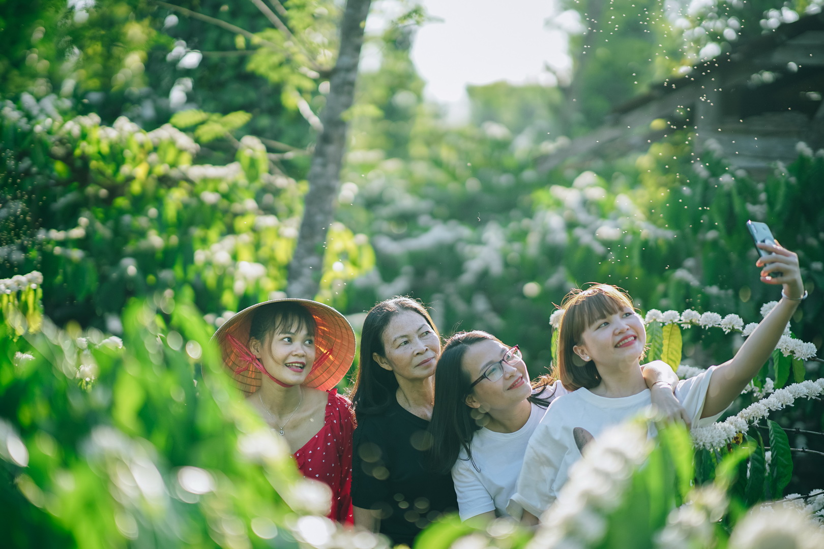 A group of women take selfies against the white blossoming coffee flowers in a Robusta garden in the Central Highland Province of Dak Lak. Photo: Van Nguyen