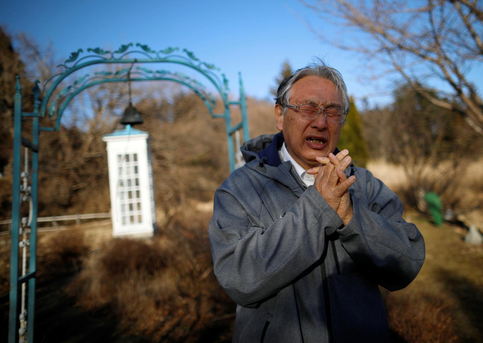 Kazuyoshi Sasaki, 67, who lost his wife, Miwako, in the March 11, 2011 earthquake and tsunami disaster, reacts as he steps out of Kazo-no-Denwa (The phone of the Wind), a phone booth set up for people to call their deceased loved ones, after calling his late wife, ahead of the 10th anniversary of when the disaster happened, at Bell Gardia Kujira-yama in Otsuchi town, Iwate Prefecture, northern Japan, February 27, 2021. Photo: Reuters