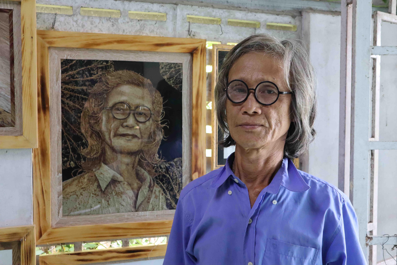 Le Van Nghia and a portrait of himself, made using lotus leaves Photo: Nam Vuong / Tuoi Tre