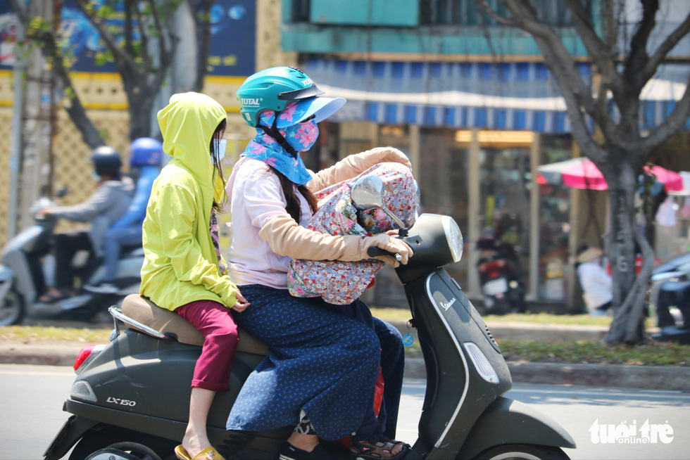 A woman carries two kids on a scooter, covered in thick clothing to avoid sunlight, in Ho Chi Minh City. Photo: Nhat Thinh / Tuoi Tre