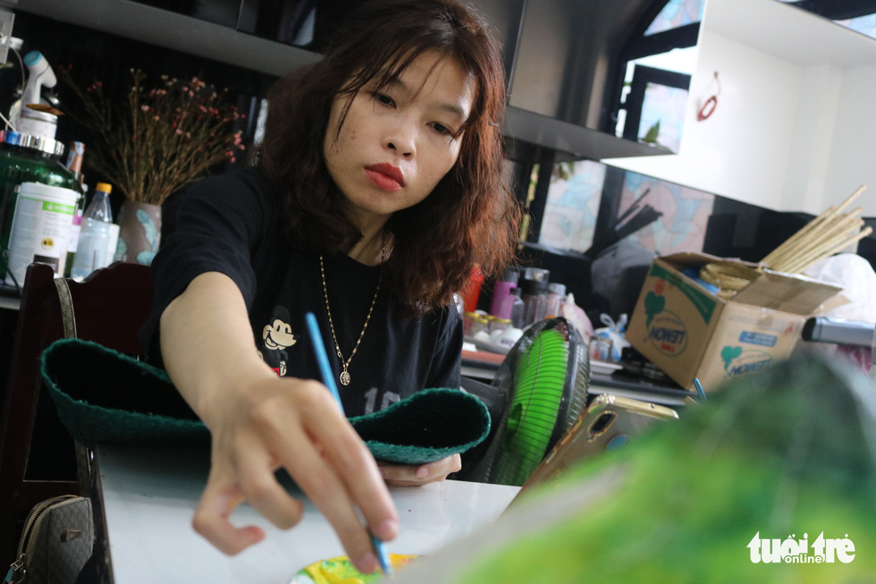 Nguyen Thi Binh, a graduate from Hue University - College of Arts, draws on a bag made from 'co bang' at a production facility owned by Ho Suong Lan in Thua Thien - Hue Province, Vietnam. Photo: Tuoi Tre