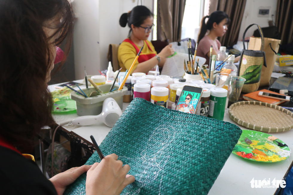 An employee draws on a bag made from 'co bang' at a production facility owned by Ho Suong Lan in Thua Thien - Hue Province, Vietnam. Photo: Tuoi Tre