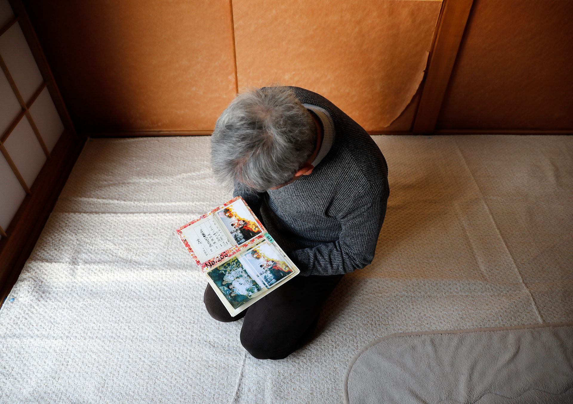 Sasaki cradles photos of his family that were damaged in the disaster and recovered by volunteers. He now lives alone after his surviving son moved out recently. They finally talked about what happened the day of the tsunami, 10 years later. Photo: Reuters