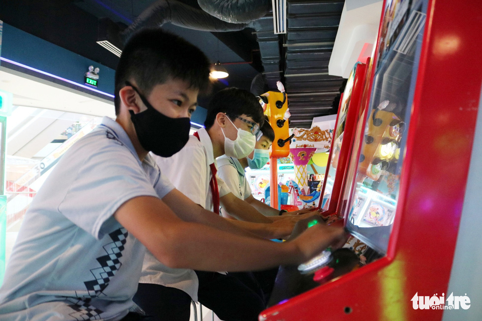 Children wearing face masks play games at a game center in Van Hanh Mall in District 10, Ho Chi Minh City, March 9, 2021. Photo: Nhat Thinh / Tuoi Tre