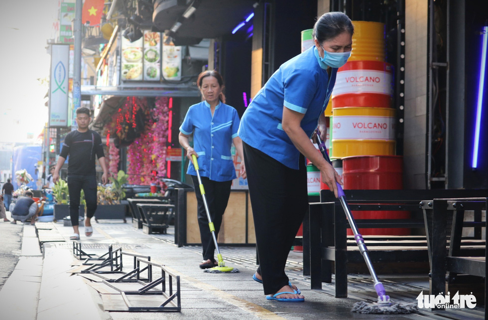 Workers clean the floor at a drinking establishment on Bui Vien Street in District 1, Ho Chi Minh City, March 9, 2021. Photo: Nhat Thinh / Tuoi Tre