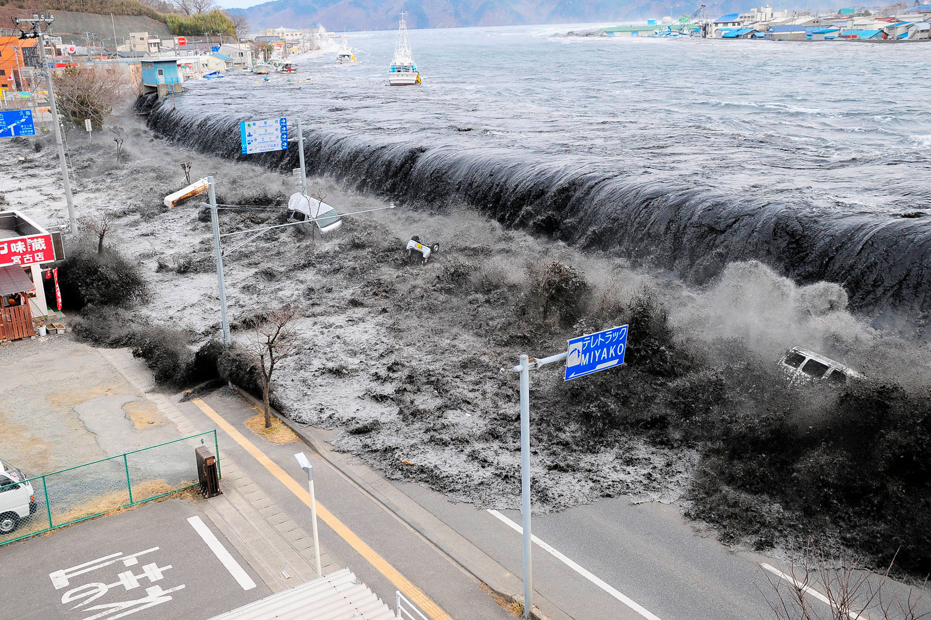 A giant wave tosses large vehicles like children's toys in the Japanese city of Miyako City after an earthquake struck the area March 11, 2011. Photo: Mainichi Shimbun/via Reuters