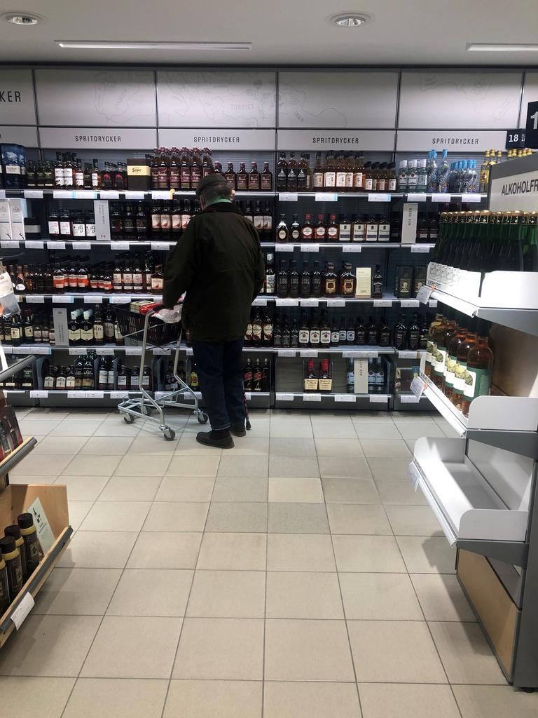 A man looks at whiskey bottles in Sweden's state-run alcohol monopoly in central Stockholm amid the coronavirus disease (COVID-19) pandemic, Sweden, March 8, 2021. Photo: Reuters
