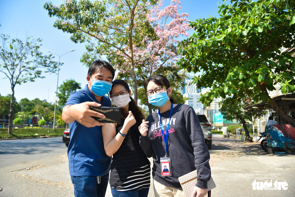 A group of friends wears face masks while taking photo with the rosy trumpet flowers. Photo: Ngoc Phuong / Tuoi Tre