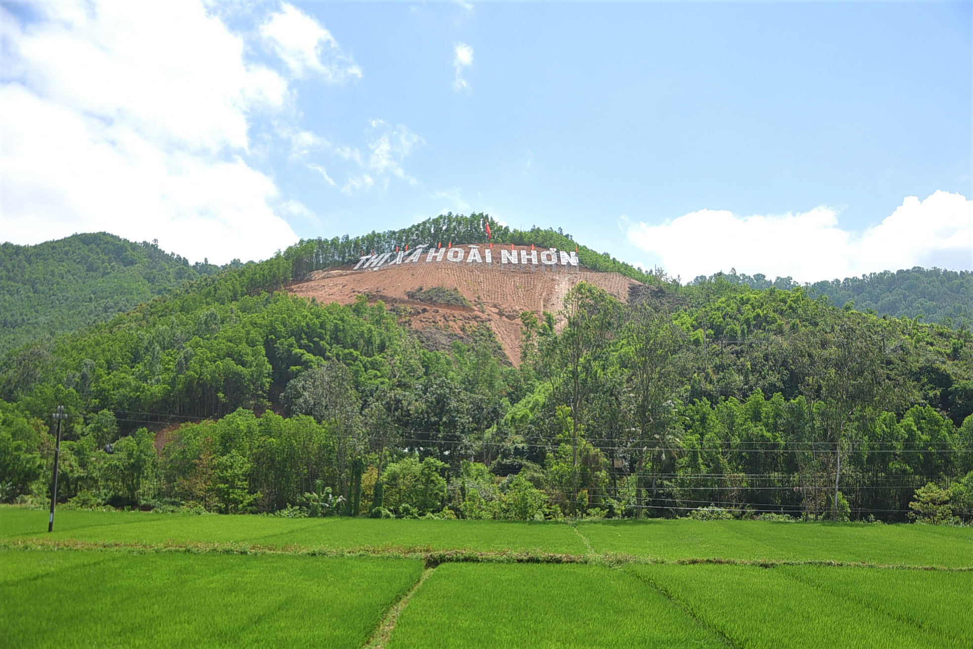 The sign advertising the name of Hoai Nhon Town is seen on a bare land lot standing out amidst other green parts of a local mountain in Binh Dinh Province, Vietnam. Photo: Lam Thien / Tuoi Tre