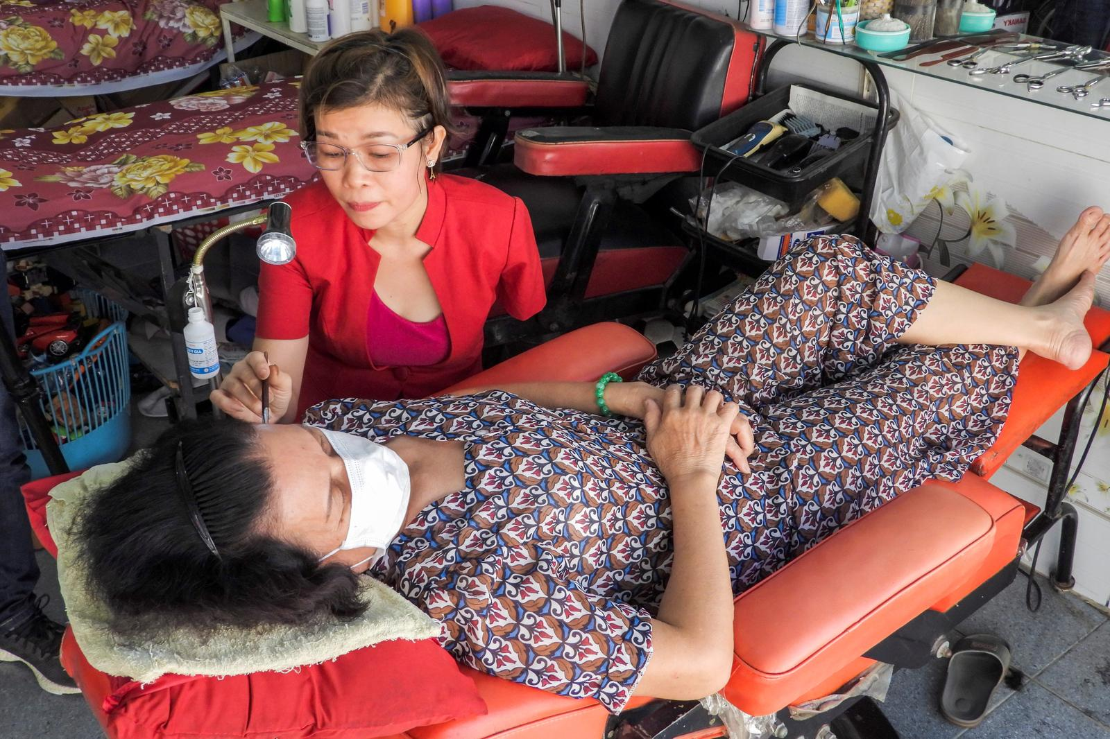 Le Thi Kim Tram, who lost her left arm in a traffic accident four years ago, works at her barbershop in Ho Chi Minh City, Vietnam March 5, 2021. Picture taken March 5, 2021. Photo: Reuters