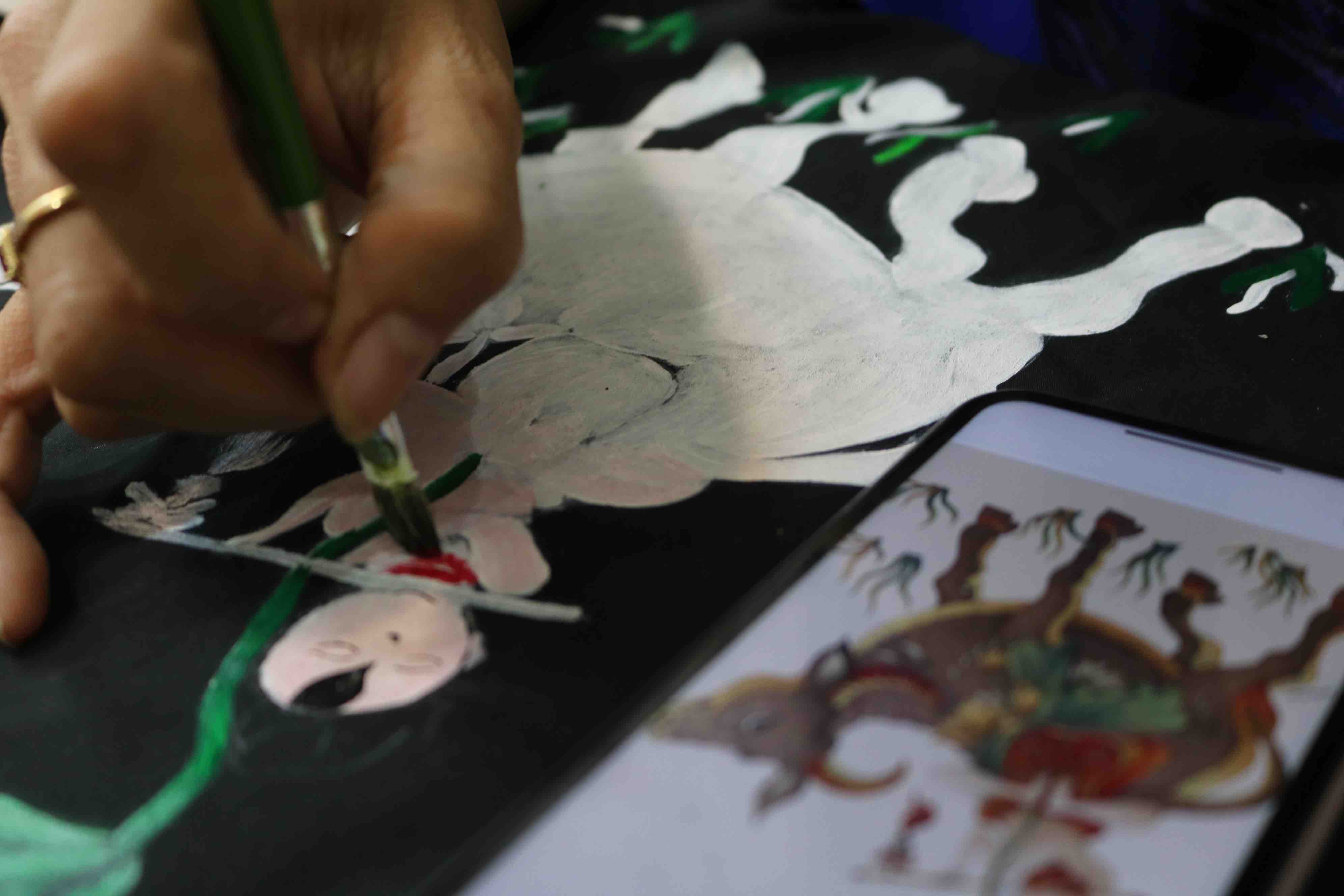 A student decorates an old T-shirt with Dong Ho folk painting pattern at Nguyen Hai Kim's workshop in Phu Nhuan District, Ho Chi Minh City. Photo: Hoang An / Tuoi Tre