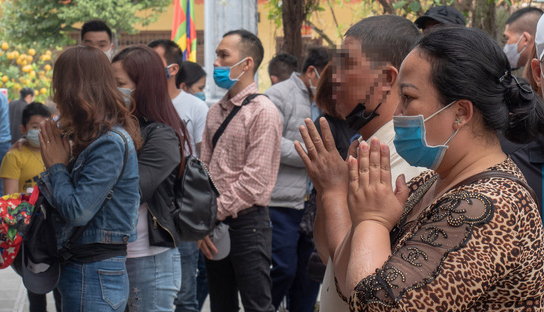 A man lowers his face mask during his visit to the Huong Pagoda Festival in Hanoi, March 13, 2021. Photo: Vu Tuan / Tuoi Tre