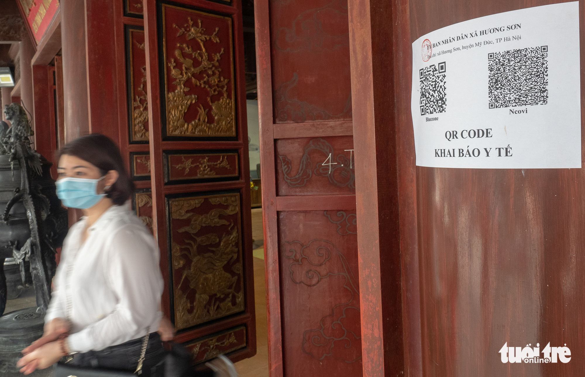 A woman walks past a paper pasted on a pillar with QR codes for online health declaration at the Huong Pagoda Festival in Hanoi, March 13, 2021. Photo: Vu Tuan / Tuoi Tre