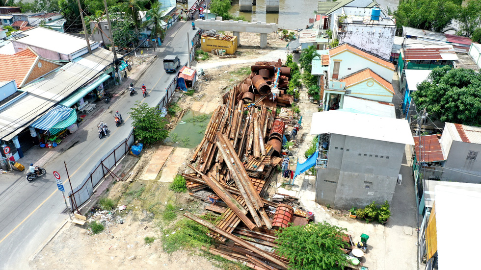 Rusty steel beams and cylinders lie across the fronts of houses along Le Van Luong Street years in Nha Be District, Ho Chi Minh City. Photo: Tu Trung / Tuoi Tre