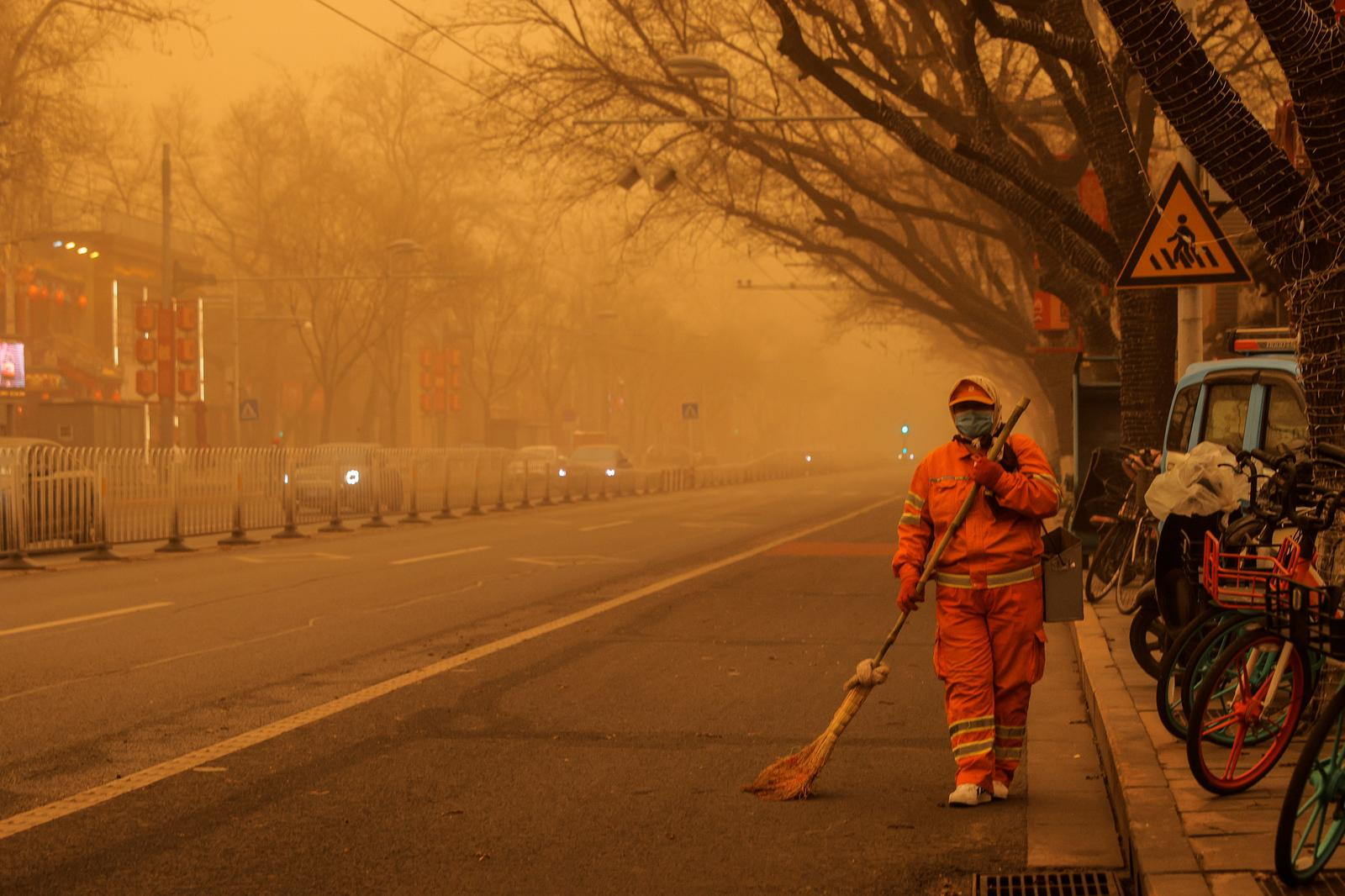 A sweeper walks with a broom along a road during morning rush hour as Beijing, China, is hit by a sandstorm, March 15, 2021. Photo: Reuters