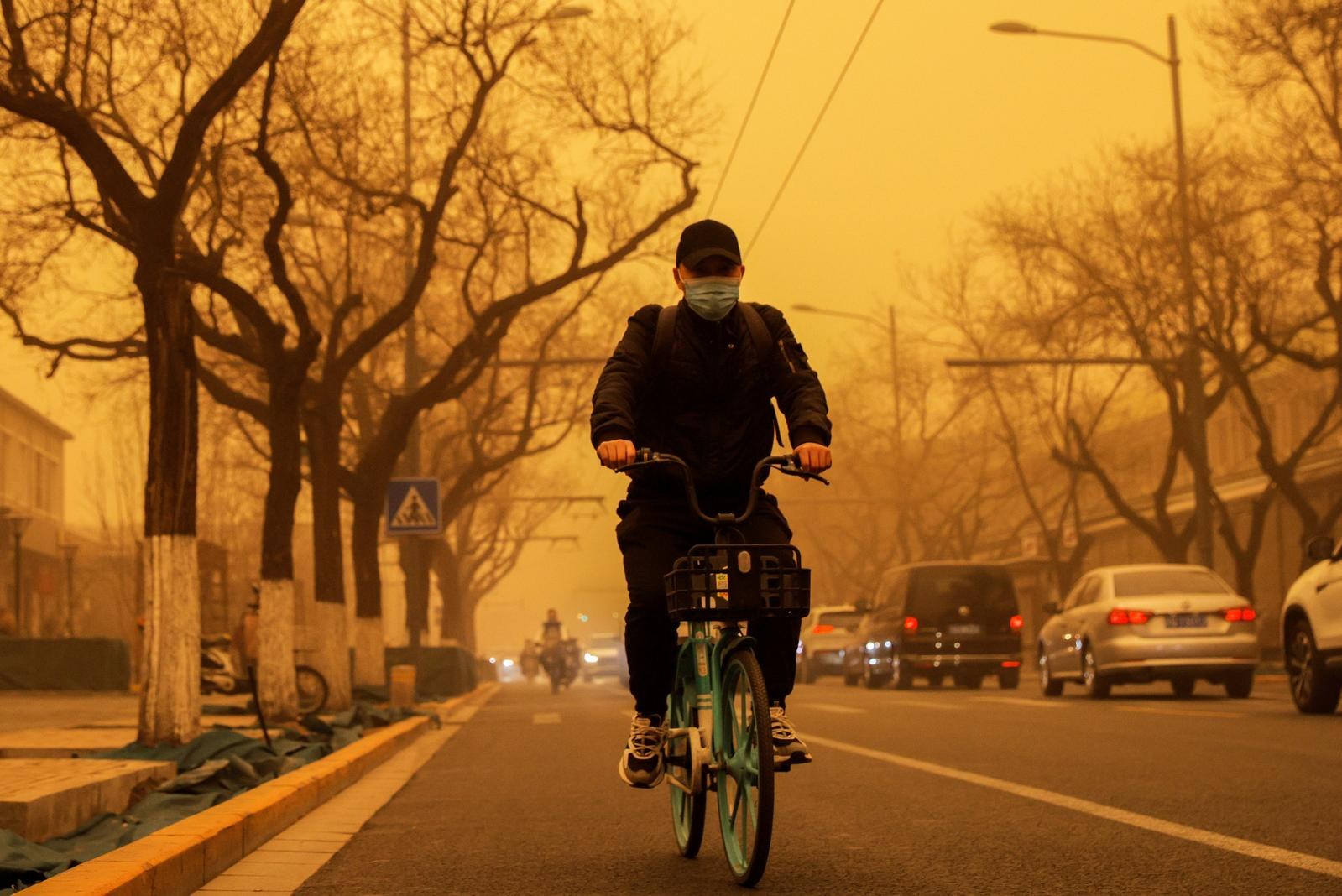 A person cycles down a road during morning rush hour as Beijing, China, is hit by a sandstorm, March 15, 2021. Photo: Reuters