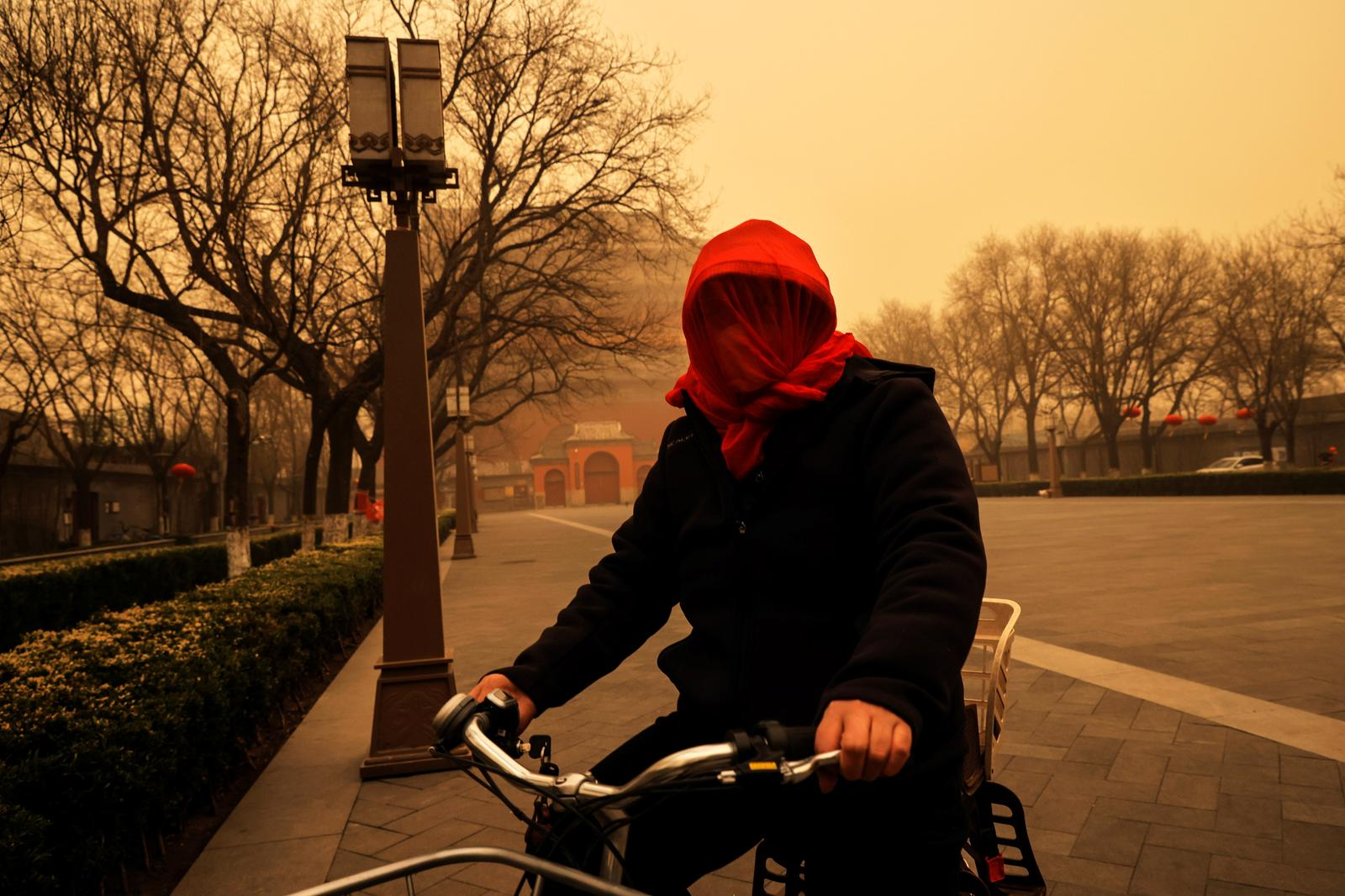 A woman cycles with her head covered during morning rush hour as Beijing, China, is hit by a sandstorm, March 15, 2021. Photo: Reuters