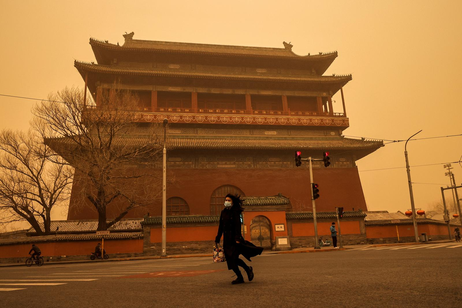 A woman walks past Drum Tower during morning rush hour as Beijing, China, is hit by a sandstorm, March 15, 2021. Photo: Reuters